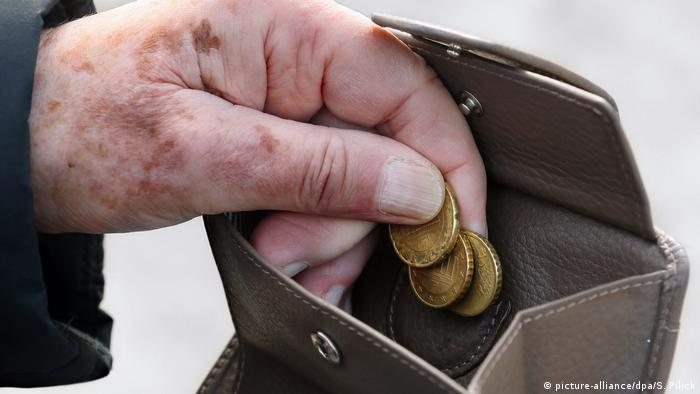 An elderly person taking coins out of a purse