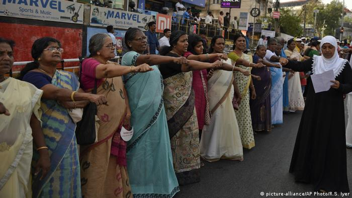 Women raise their right hands while protesting in Kerala