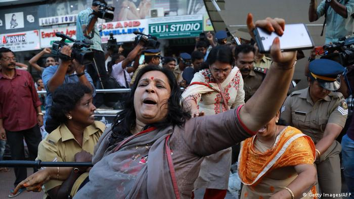 A woman holds up her cellphone surrounded by police in Kochi (Getty Images/AFP)