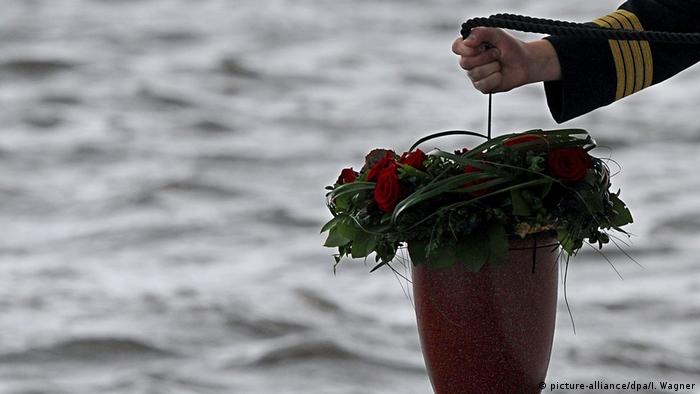 An urn being lowered for a sea burial