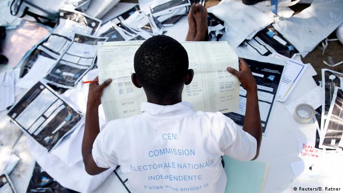 A man examines voting materials at a vote tallying center in Kinshasa (Reuters/B. Ratner)