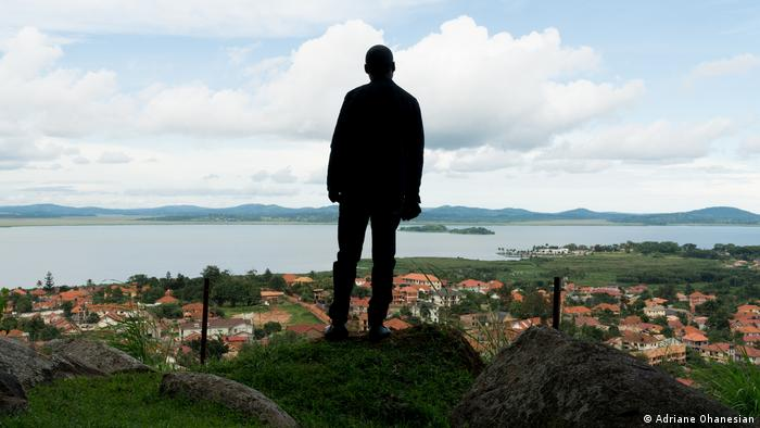 The sillhouette of Faustin stands overlooking a town in Uganda