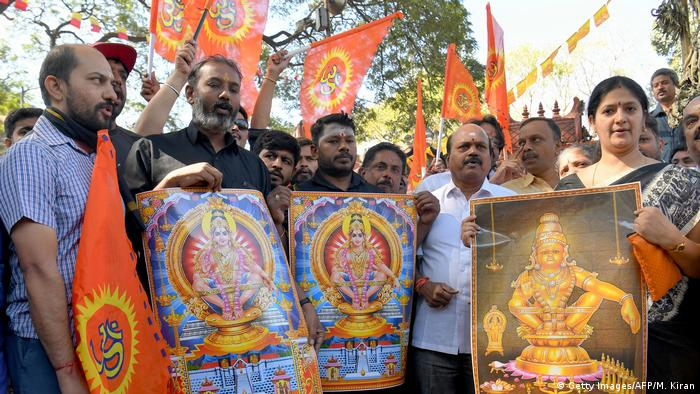 Hindu traditionalists, including one woman, hold up placards with the image of celibate deity Ayyappa