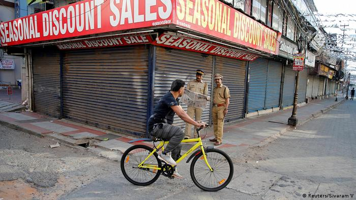 Man bikes past shops in the city of Kochi