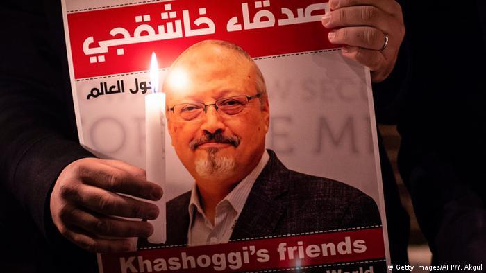 Picture of Jamal Khashoggi beside a man holding a candle