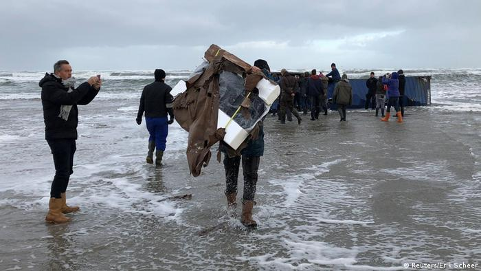 A person carries a flat-screen television set as others inspect a cargo container after it washed up on a beach (Reuters/Erik Scheer)