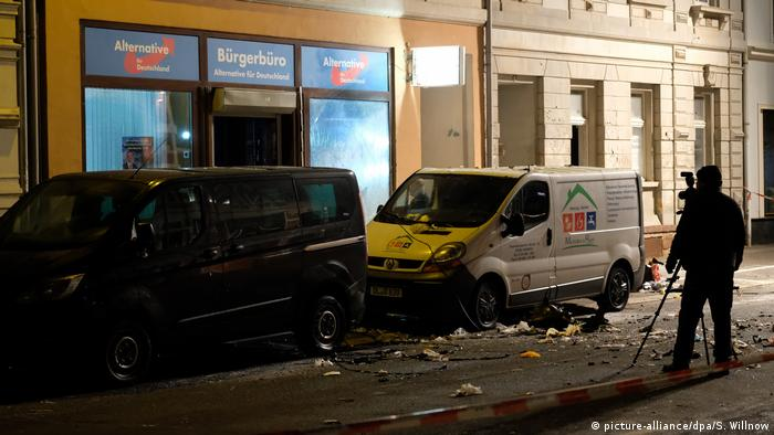 A man takes pictures of the damaged AFD office in Döbeln