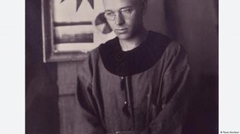 Photo of a man with round wire-rimmed glasses wearing a painter's cape with a round collar, taken in Weimar in 1920 or 1921