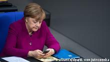 ARCHIV - 19.01.2018, Berlin: Bundeskanzlerin Angela Merkel (CDU) sitzt in der Plenarsitzung des Deutschen Bundestages in Berlin und hält ihr Smartphone in der Hand. (zu dpa:Bundeskanzlerin Merkel auch von Daten-Angriff betroffen vom 04.01.2019) Foto: Bernd von Jutrczenka/dpa +++ dpa-Bildfunk +++ | Verwendung weltweit