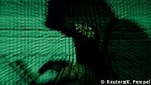 FILE PHOTO: A man holds a laptop computer as cyber code is projected on him in this illustration picture taken on May 13, 2017. Capitalizing on spying tools believed to have been developed by the U.S. National Security Agency, hackers staged a cyber assault with a self-spreading malware that has infected tens of thousands of computers in nearly 100 countries. REUTERS/Kacper Pempel/Illustration/File Photo