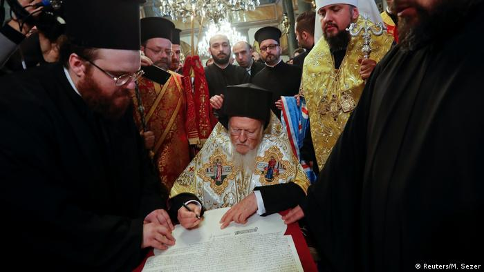 Patriarch Bartholomew signs the document granting independence to the Ukrainian Orthodox church (Reuters/M. Sezer)