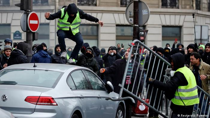 A protester jumps on a car in Paris (Reuters/G. Fuentes)