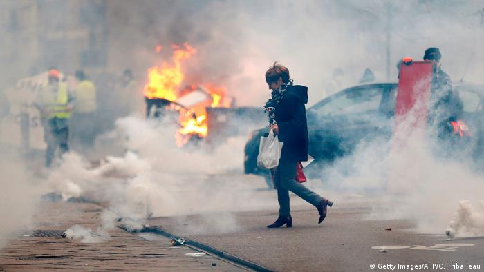 woman walks through smoke passing burning material during a rally by Yellow Vest (Gilets jaunes) anti-government protesters in Rouen