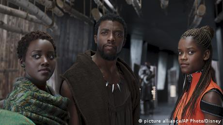 Szene aus Black Panther mit drei schwarzen Darstellern, die in die Kamerarichtung blicken (picture alliance/AP Photo/Disney)