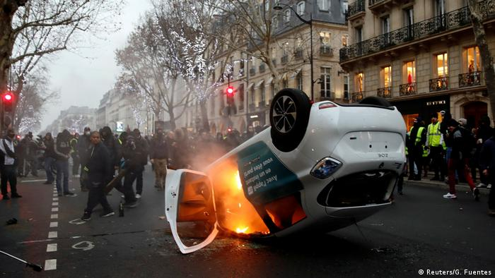 An overturned car burns during a demonstration by the yellow vests movement at Boulevard Saint Germain in Paris