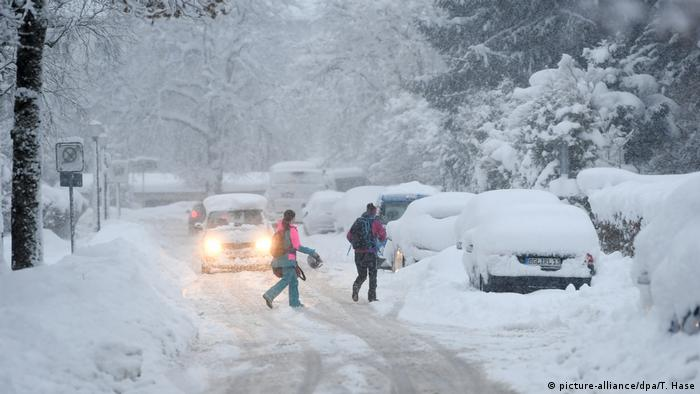 People outside snow covered cars on a snowy street