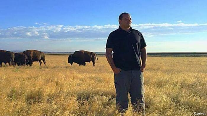Jason Baldes stands amidst the tall grass of the prairie as bison roam in the background