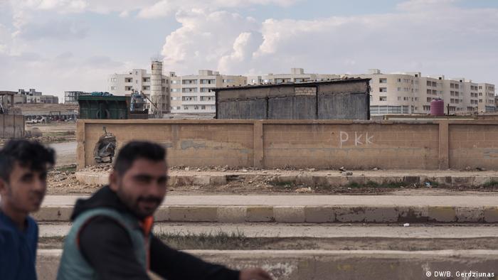 Two men in front of a wall (DW/B. Gerdziunas)