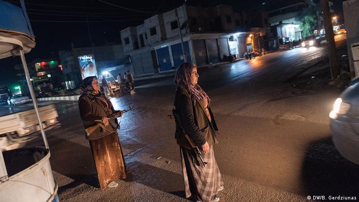 Two armed women on the streets in Kobane (DW/B. Gerdziunas)