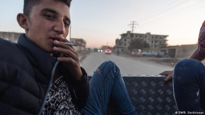 A man smoking a cigarette on the back of a truck (DW/B. Gerdziunas)