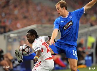 لاعب شتوتغارت أرتو بوكا يخطف الكرة من لاعب غلاسكو ستيفن وايتيكر