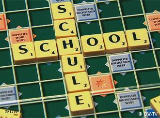 Auf einem Scrabble-Spielbrett kreuzen sich die Wörter Schule und school (Foto: DW-TV)