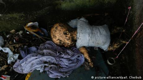 A dirty doll lies on the ground