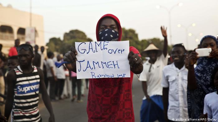 Man holds banner with Game over Jammeh written on as Gambians cheer in Serrekunda