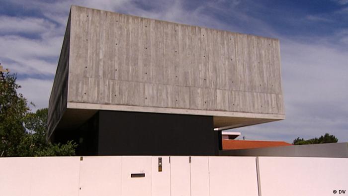 Zu sehen ist ein Beton-Kader auf einem etwas kleineren schwarzen Quader. Alles eingerahmt von einem weiß Zaum. Und tatsächlich ist nirgendwo ein Fenster zu sehen.
