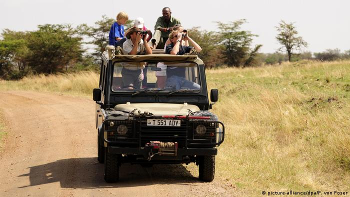 An open-topped Land Rover with tourists in the Serengeti National Park