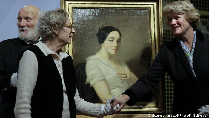 Government Commissioner for Culture and the Media Monika Grütters, right, hands over the painting 'Portrait of a Seated Young Woman' by Thomas Couture to Mandel's heirs