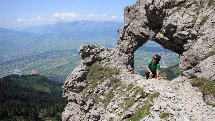 A hiker climbing through a hole in a rock on a mountain side in Liechtenstein