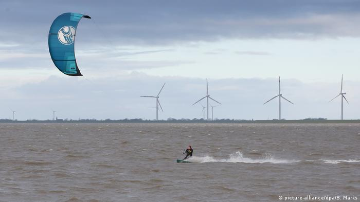 A kite surfer riding waves ahead of the storm