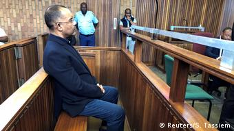 Former Mozambican Finance Minister Manuel Chang sits on a bench in a South African courtroom (Reuters/S. Tassiem)