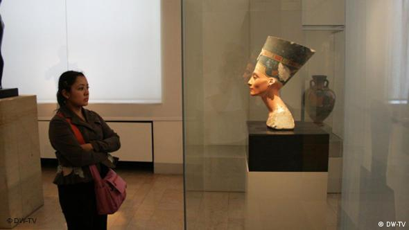 A visitor looks at the bust of Nefertiti Berlin's Neues Museum