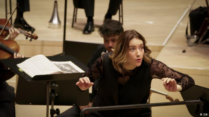 Alondra de la Parra conducting and seemingly whispering an unknown message to her musicians (DW)
