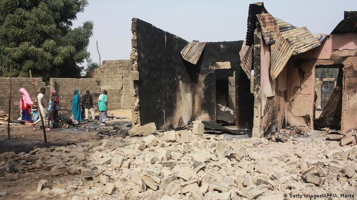 People walk in the rubble of a house destroyed in a Boko Haram attack
