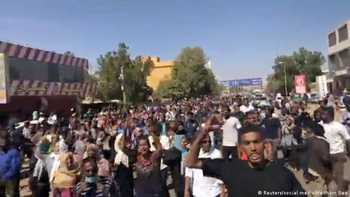 Hundreds of people walk down a street, many with their arms raised in protest