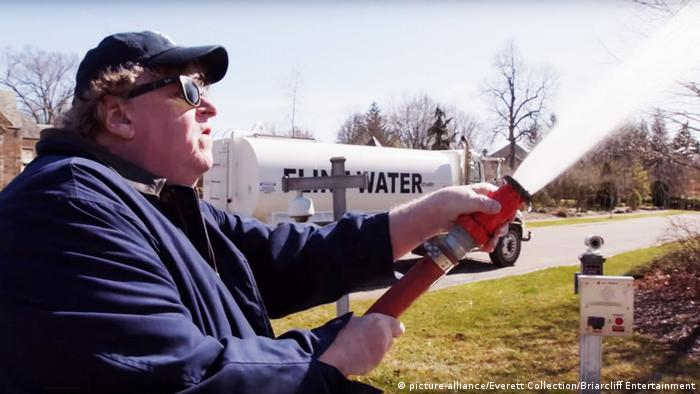 Michael Moore spraying Flint water on the lawn of Michigan Governor Rick Snyder