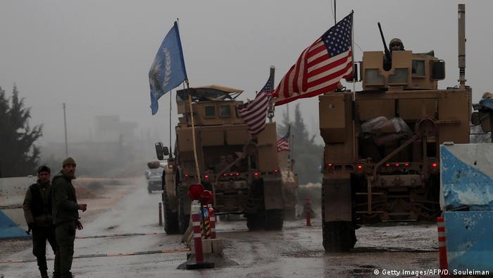 Veículos militares com a bandeira dos Estados Unidos em uma estrada.