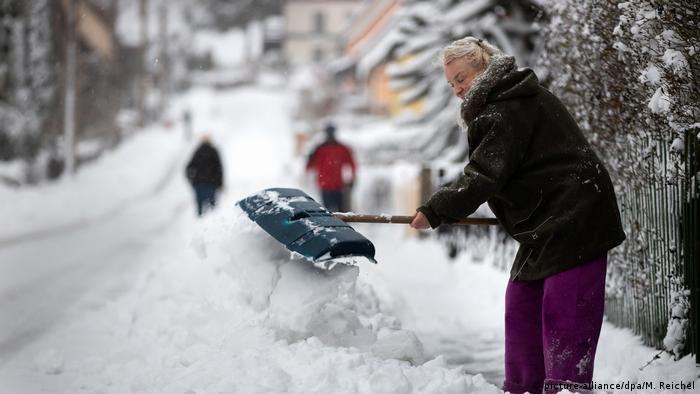 A woman shovels snow