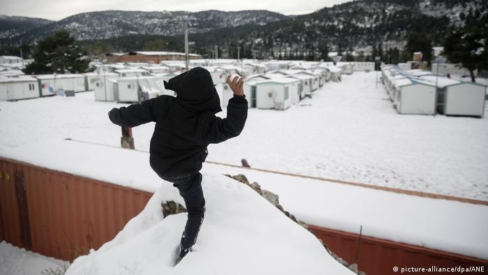 A refugee child throws a snowball