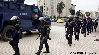 Police in riot gear walk near Congo's electoral commission headquarters