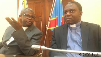 Donatien Nsholé (left with glasses) gestures with his left arm alongside Jean Marie Bomengola, Congolese Catholic church spokesperson (DW/W. Bashi)