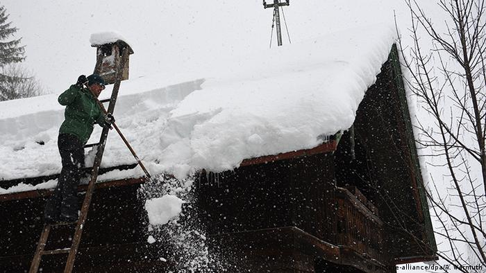 A man removes snow from a roof (picture-alliance/dpa/A. Warmuth)