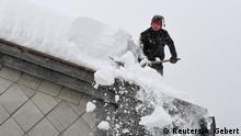 Deutschland, Inzell: Mann entfernt Schnee vom Hausdach