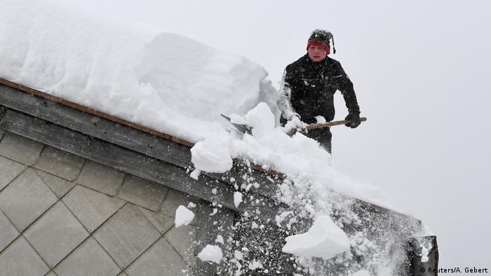 Deutschland, Inzell: Mann entfernt Schnee vom Hausdach (Reuters/A. Gebert)
