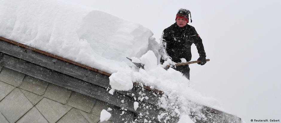 Homem remove camada de neve do telhado de sua casa em Inzell, na Alta Baviera