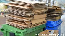 Mülltonnen mit Pappe stehen zur Abholung von der Müllabfuhr auf einem Gehweg in Hannover bereit, aufgenommen am 06.01.2014. Foto: Frank May   Verwendung weltweit