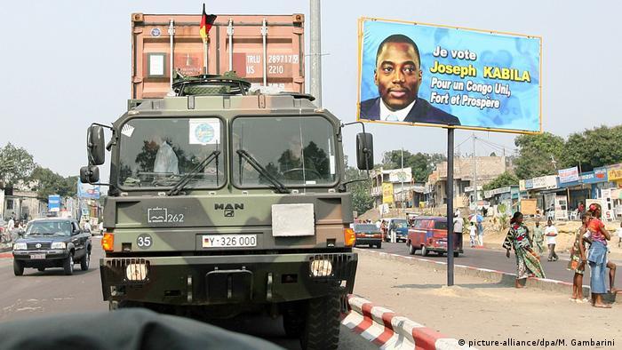 Ein Bundeswehr-Laster fährt an einem Wahlplakat für Präsident Kabila 2006 in Kinshasa vorbei (picture-alliance/dpa/M. Gambarini )